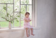 Little girl on old windowsill with spring flowers. Beautiful little girl on old windowsill with spring flowers stock image