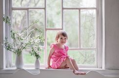 Beautiful little girl on old windowsill with spring flowers. The beautiful little girl on old windowsill with spring flowers royalty free stock image