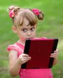 Beautiful little girl outdoor with tablet pc on Stock Images