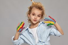 Beautiful little girl with a painted fingers is posing on a gray background. Pretty little girl having a brush in her chic curly blond hair, wearing in a blue stock photography