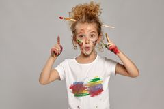 Beautiful little girl with a painted fingers is posing on a gray background. Wondered little girl having a brush in her chic curly blond hair, wearing in a stock image