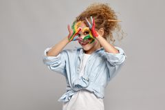 Beautiful little girl with a painted hands and cheeks is posing on a gray background. Charming girl having a brush in her chic curly blond hair, wearing in a royalty free stock photography