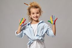 Beautiful little girl with a painted hands is posing on a gray background. Beautiful kid having a brush in her chic curly blond hair, wearing in a blue shirt royalty free stock photo