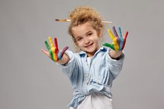 Beautiful little girl with a painted hands is posing on a gray background. Lovely child having a brush in her chic curly blond hair, wearing in a blue shirt and stock photos