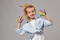 Beautiful little girl with a painted hands is posing on a gray background. Lovely girl having a brush in her chic curly blond hair, wearing in a blue shirt and stock photos