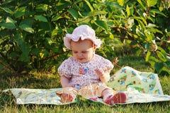 Beautiful little girl in panama sitting on meadow Stock Photo