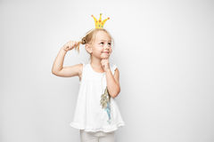 Beautiful little girl with paper crown posing on white background at home. Royalty Free Stock Photography