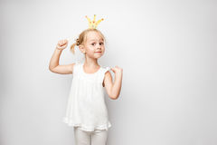 Beautiful little girl with paper crown posing on white background at home. Royalty Free Stock Photo
