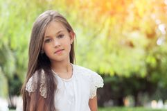 Beautiful little girl in the park, with long hair and and a sweet, gentle look. Happy childhood concept. stock photos