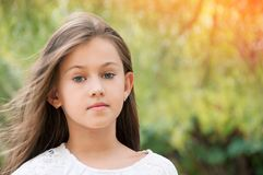 Beautiful little girl in the park, with long hair and and a sweet, gentle look. Happy childhood concept. stock photo
