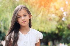 Beautiful little girl in the park, with long hair and and a sweet, gentle look. Happy childhood concept. royalty free stock photography
