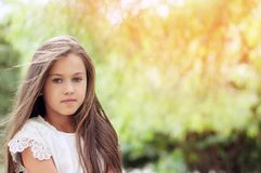 Beautiful little girl in the park, with long hair and and a sweet, gentle look. Happy childhood concept. stock images