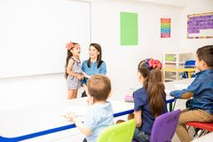 Preschool student reciting a poem. Beautiful little girl participating in class and reciting a poem in a preschool classroom stock image