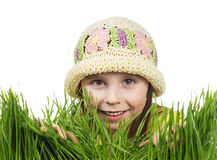 Beautiful little girl peeking out of the grass. On a white background Royalty Free Stock Photos