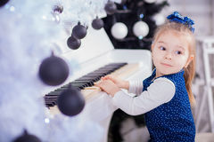 Beautiful little girl piano and looking at camera Stock Photography
