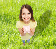 Beautiful little girl with piggy bank Stock Image