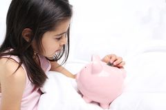 Girl with piggy bank. Beautiful little girl with piggy bank on white bed Stock Photo