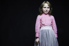 Beautiful little girl in a pink blouse and white skirt Stock Images