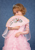 Beautiful little girl in pink dress with a fan Royalty Free Stock Image