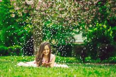 Little girl on green grass with petals. Beautiful little girl in pink dress with long brunette hair and smiling face lying on green grass in spring flower Stock Photos