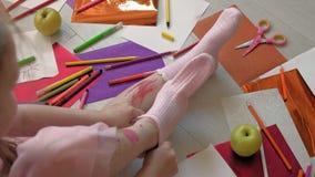 Little girl draws on her feet with felt-tip pens, children`s creativity, development. Beautiful little girl in a pink dress sitting on the floor draws felt-tip stock video