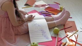 Little girl draws with pencils, children`s creativity, development. Beautiful little girl in a pink dress sitting on the floor draws with pencils and felt-tip stock footage