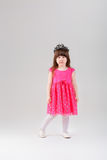 Beautiful little girl in pink Princess dress with crown on gray Stock Photo