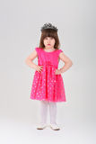 Beautiful little girl in pink Princess dress with crown on gray Stock Images