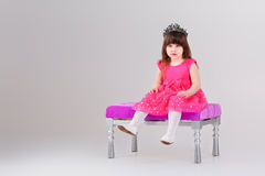 Beautiful little girl in pink Princess dress with crown sitting. Beautiful little brunette girl in pink Princess dress with crown sitting on a pink chair on gray Royalty Free Stock Image