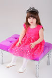 Beautiful little girl in pink Princess dress with crown sitting. Beautiful little brunette girl in pink Princess dress with crown sitting on a pink chair on gray Stock Photos