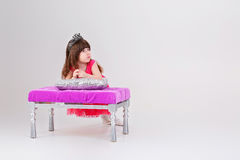 Beautiful little girl in pink Princess dress with crown sitting. Beautiful little brunette girl in pink Princess dress with crown sitting on a pink chair on gray Royalty Free Stock Photography