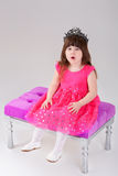 Beautiful little girl in pink Princess dress with crown sitting. Beautiful little brunette girl in pink Princess dress with crown sitting on a pink chair on gray Royalty Free Stock Photos