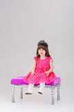Beautiful little girl in pink Princess dress with crown sitting. Beautiful little brunette girl in pink Princess dress with crown sitting on a pink chair on gray Stock Photography
