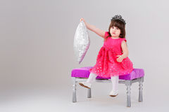 Beautiful little girl in pink Princess dress with crown sitting. Beautiful little brunette girl in pink Princess dress with crown sitting on a pink chair and Royalty Free Stock Photography
