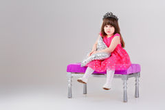 Beautiful little girl in pink Princess dress with crown sitting. Beautiful little brunette girl in pink Princess dress with crown sitting on a pink chair and Royalty Free Stock Images