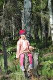 Beautiful little girl in pink sits on tree stump Stock Images