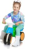 Beautiful little girl on a plastic bike. Isolated on white background Royalty Free Stock Photos