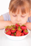 Beautiful little girl and plate with strawberries Royalty Free Stock Photo