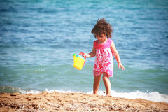 Beautiful little girl playing on the beach Stock Photo