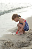Beautiful little girl playing on the beach. Royalty Free Stock Photos