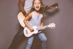 Beautiful little girl playing guitar with her father. royalty free stock photo