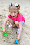 Beautiful little girl playing in a sandbox, a photo close up. Active dry baby, bright summer photo Stock Image