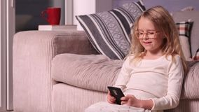 Beautiful little girl playing with smartphone Royalty Free Stock Photography