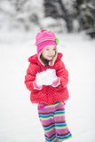 Beautiful little girl playing and throwing a snowball stock photo