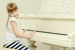 Beautiful little girl is playing on a white grand piano. A nice little girl is playing on a big white piano. The concept of musical and aesthetic education of a Stock Photos