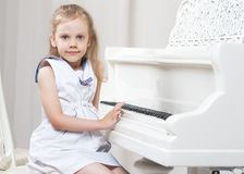 Beautiful little girl is playing on a white grand piano. A nice little girl is playing on a big white piano. The concept of musical and aesthetic education of a Stock Image