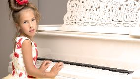 Beautiful little girl is playing on a white grand piano. Stock Image