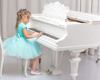 Beautiful little girl is playing on a white grand piano. A nice little girl is playing on a big white piano. The concept of musical and aesthetic education of a Stock Photo