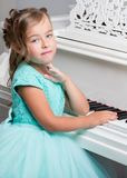 Beautiful little girl is playing on a white grand piano. A nice little girl is playing on a big white piano. The concept of musical and aesthetic education of a Royalty Free Stock Photo