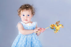 Beautiful little girl playing with a wind toy. On light blue background Stock Images